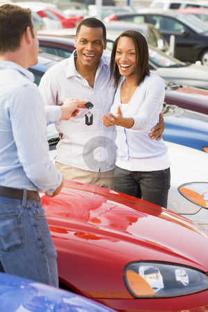 Couple picking up new car from salesman stock photo, Couple collecting new car keys from salesman on lot by Monkey Business Images