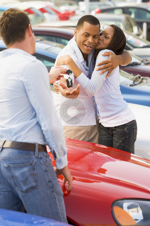 Couple collecting new car from salesman stock photo, Couple collecting new car from salesman on lot by Monkey Business Images