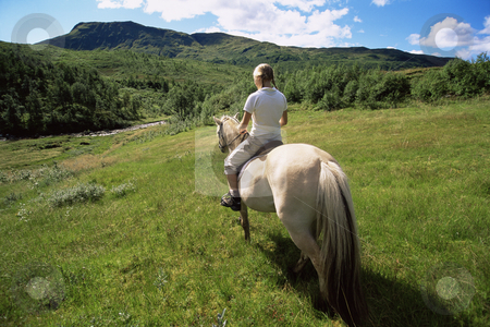 Rear view of young woman riding horse in rural setting stock photo,  by Monkey Business Images