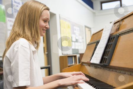 Schoolgirl playing piano in music class stock photo,  by Monkey Business Images