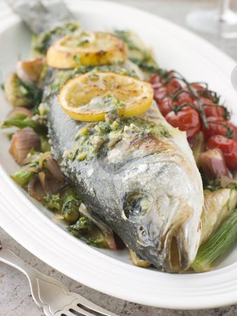 Whole Roasted Sea Bass with Fennel Lemon Cherry Vine Tomatoes an stock photo, Plate of Whole Roasted Sea Bass with Fennel Lemon Cherry Vine Tomatoes and Salsa Verde by Monkey Business Images