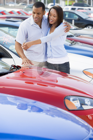 Young couple looking at new cars stock photo, Young couple looking at new cars on lot by Monkey Business Images