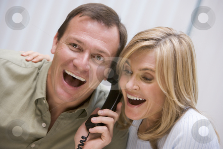 Couple receiving good news over the phone stock photo, Couple receiving good news over the phone at home by Monkey Business Images