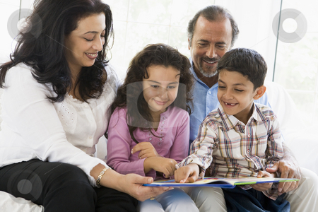 A Middle Eastern couple reading with their grandchildren stock photo,  by Monkey Business Images