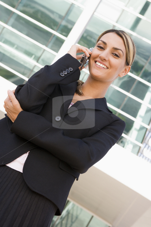 Businesswoman standing outdoors on cellular phone smiling stock photo,  by Monkey Business Images