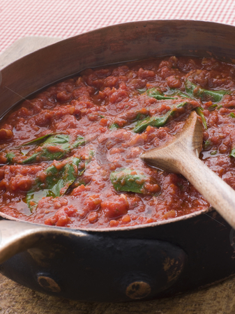 Pan of Fresh Tomato Sauce stock photo, Pan of Fresh Tomato Sauce with wooden spoon by Monkey Business Images