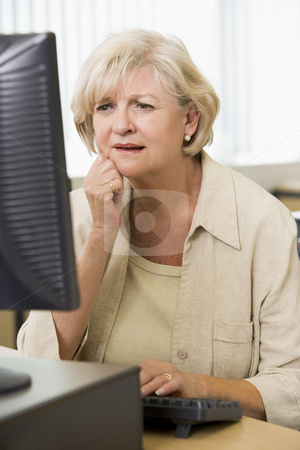 Confused woman frowning at computer monitor stock photo,  by Monkey Business Images