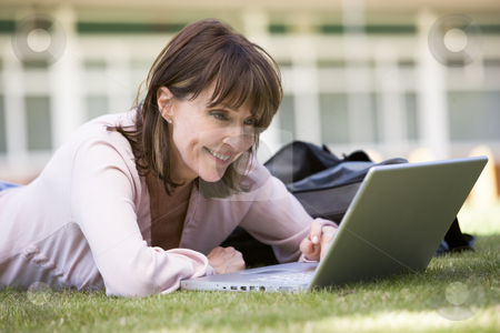 Woman using laptop on campus stock photo,  by Monkey Business Images