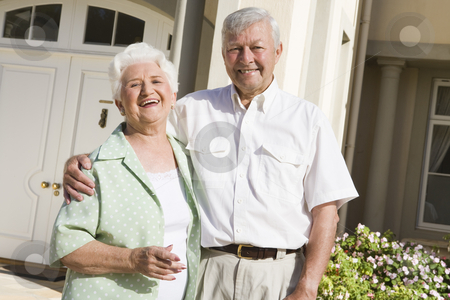 Senior couple standing outside house stock photo, Senior couple standing outside front door of home by Monkey Business Images