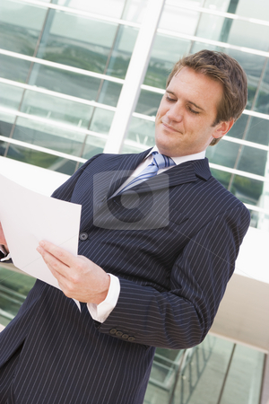 Businessman standing outdoors looking at paperwork stock photo,  by Monkey Business Images