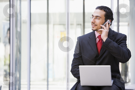 Businessman using laptop and mobile phone outside stock photo, Businessman using laptop and mobile phone outside office by Monkey Business Images