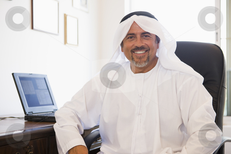 A Middle Eastern man sitting in front of a computer at home stock photo,  by Monkey Business Images