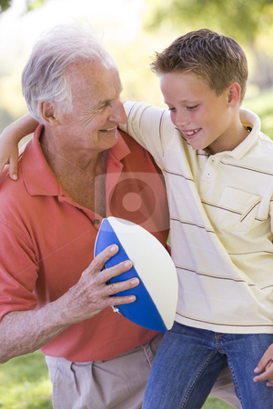 Grandfather and grandson outdoors with football smiling stock photo,  by Monkey Business Images