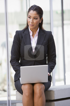 Businesswoman using laptop outside stock photo, Businesswoman using laptop outside office by Monkey Business Images