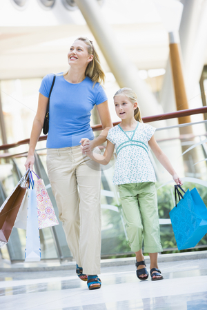 Mother and daughter shopping in mall stock photo, Mother and daughter in shopping mall carrying bags by Monkey Business Images