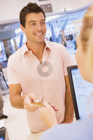 Man making purchase with credit card stock photo, Man making purchase with credit card in shop by Monkey Business Images