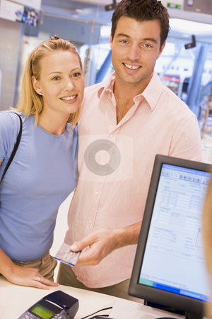 Couple making purchase with credit card stock photo, Couple making purchase with credit card in store by Monkey Business Images