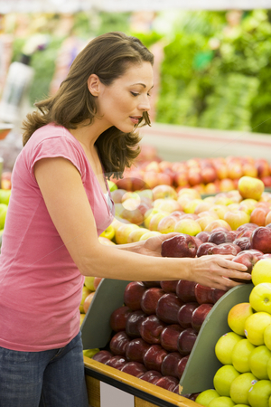 Woman choosing apples in produce department stock photo, Woman choosing apples in produce department of supermarket by Monkey Business Images