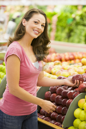 Woman choosing apples at produce counter stock photo, Woman choosing apples at produce counter of supermarket by Monkey Business Images