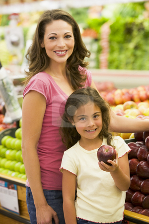 Mother and daughter buying fresh fruit stock photo, Mother and daughter buying fresh fruit in supermarket by Monkey Business Images