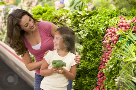 Mother and daughter choosing fresh produce stock photo, Mother and daughter choosing fresh produce in supermarket by Monkey Business Images
