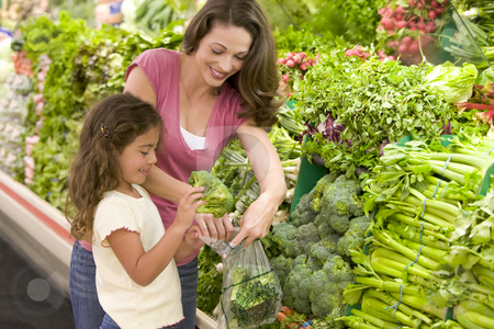 Mother and daughter shopping for produce stock photo, Mother and daughter shopping for produce in supermarket by Monkey Business Images