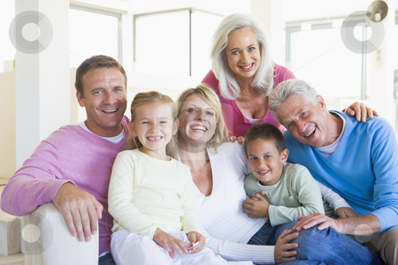 Family sitting indoors smiling stock photo,  by Monkey Business Images