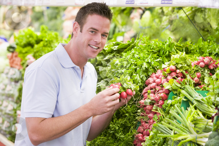 Young man shopping for fresh produce stock photo, Young man shopping for fresh produce in supermarket by Monkey Business Images