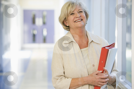 A woman with a ringbinder standing in a campus corridor stock photo,  by Monkey Business Images