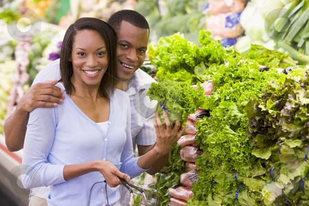 Couple buying fresh produce stock photo, Couple buying fresh produce in supermarket by Monkey Business Images