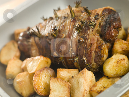 Roast Leg of Lamb Studded with Garlic and Rosemary and Roast Pot stock photo, Roasting tin of Roast Leg of Lamb Studded with Garlic and Rosemary and Roast Potatoes by Monkey Business Images