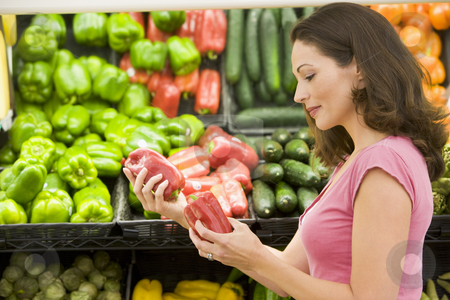 Woman choosing fresh produce stock photo, Woman choosing fresh produce in supermarket by Monkey Business Images