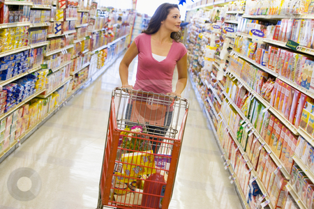 Young woman grocery shopping stock photo, Young woman grocery shopping in supermarket by Monkey Business Images