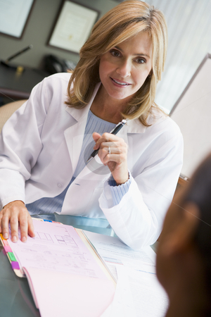 Doctor in discussion with patient in IVF clinic stock photo, Woman in discussion with patient in IVF clinic seated at desk by Monkey Business Images