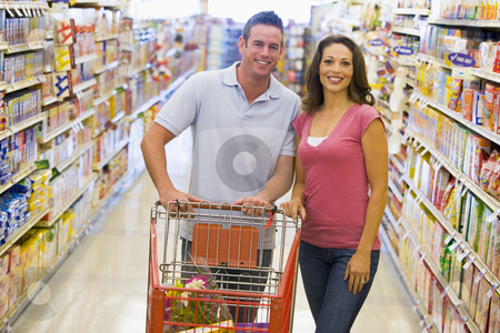 Young couple grocery shopping stock photo, Young couple grocery shopping in supermarket by Monkey Business Images