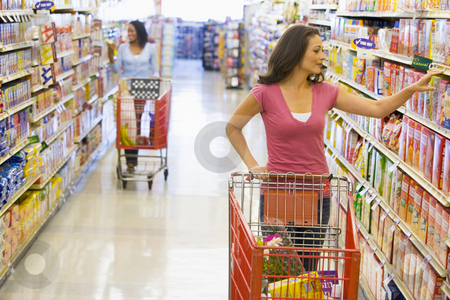 Women grocery shopping stock photo, Women grocery shopping in supermarket by Monkey Business Images