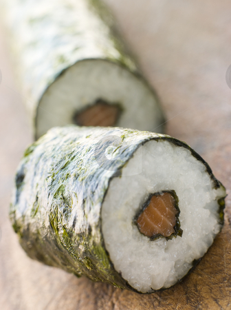 Roll of Salmon Sushi on a Board stock photo, Close up of Roll of Salmon Sushi on a Board by Monkey Business Images