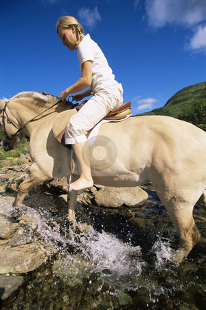 Young woman crossing a river by horse stock photo,  by Monkey Business Images
