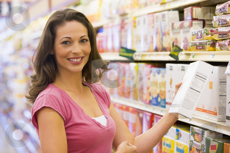Woman grocery shopping stock photo, Woman grocery shopping in supermarket by Monkey Business Images