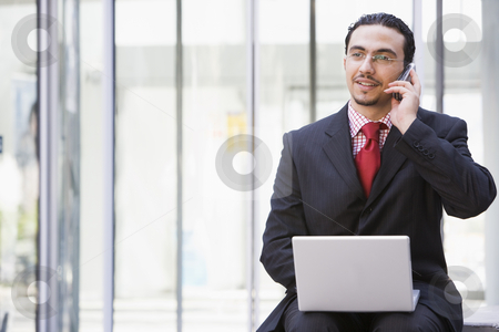 Businessman using laptop and mobile phone outside stock photo, Businessman using laptop and mobile phone outside by Monkey Business Images