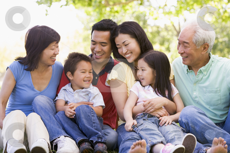 Extended family sitting outdoors smiling stock photo,  by Monkey Business Images