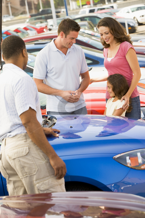 Family choosing new car stock photo, Family choosing new car on lot by Monkey Business Images