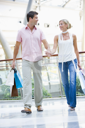 Young couple shopping in mall stock photo, Young couple shopping in mall carrying bags by Monkey Business Images