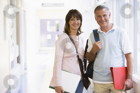 A man and woman with backpacks standing in a campus corridor stock photo,  by Monkey Business Images