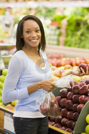 Young woman shopping for fresh produce stock photo, Young woman shopping for fresh produce in supermarket by Monkey Business Images