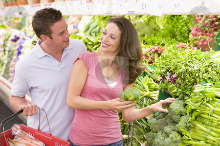 Young couple shopping for fresh produce stock photo, Young couple shopping for fresh produce in supermarket by Monkey Business Images