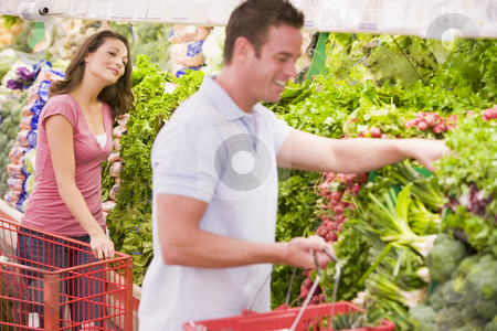 Young couple flirting in supermarket aisle stock photo, Young couple flirting in supermarket aisle by Monkey Business Images