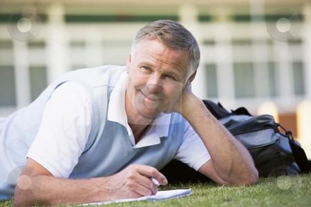 A man writing notes while lying on a campus lawn stock photo,  by Monkey Business Images