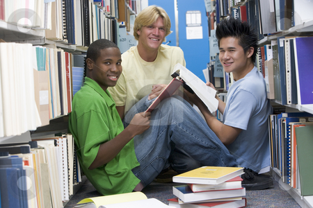 Group of university students working in library stock photo, Group of three male students sitting on floor of library surrounded by books by Monkey Business Images