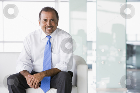 Businessman sitting on sofa in lobby stock photo, Businessman sitting on sofa in office lobby by Monkey Business Images